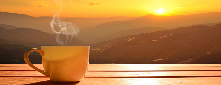 welcome hot coffee cup on table viewing sunrise mountains