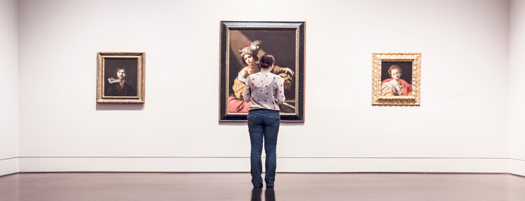 girl standing in front of painting in gallery