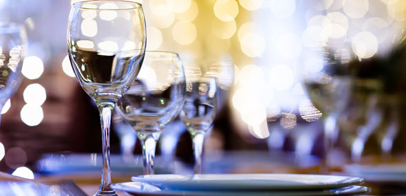 Set table with wine glasses in fancy restaurant, with holiday lights in the background